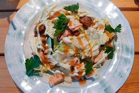 Салат тайский с курицей забавный. Несколько кусочков свежего ананаса и птицы покрыли слоем сухих листьев пекинской капусты, которые полили полосками соуса, похожего на сладкий чили