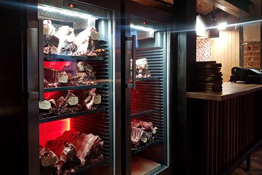 Холодильники с мясом стоят взале, наполненные стейками, маркированными подате ивиду