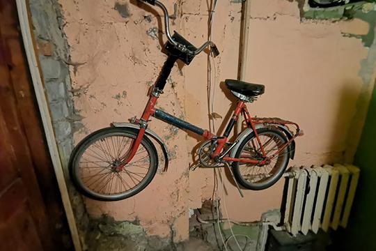 На стенах — облупившаяся краска, на полу — потертый кафель. Здесь же чугунные непокрашенные батареи и прибитый к стене старый велосипед
