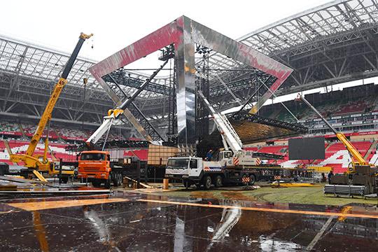 Декорационная застройка стадиона началась еще в июне. Порядка 600 рабочих, несмотря на погодные условия, не прекращают работы – монтируют сцены, отлаживают звуковое и видеопроекционное оборудование