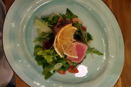 Стейк из тунца здесь правильного ярко-розового цвета. Он подается с салатом из имбирной репы и сельдерея, и обсыпан кунжутом. Хорошее сочетание, и не стоит бояться, что рыба «недоготовленная» — именно таким и должен быть тунец