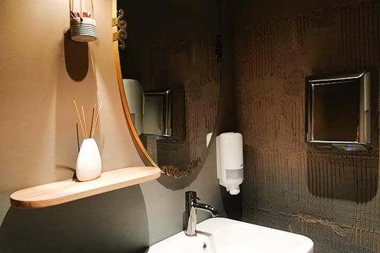 Приятное впечатление оставляет уборная: несколько небрежные голубовато-розовые градиентные стены классно сочетаются состаринным зеркалом сзавитками