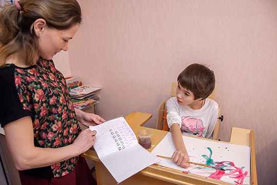 Милана особенно любит рисовать Чтобы обеспечить дочери нужное положение за столом родители фиксируют ее тело специальными приспособлениями