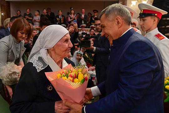 Рустам Минниханов, одетый втрадиционный татарский костюм своротником стойкой, перед тем как спуститься впервый ряд зала, чтобы поздравить женщин-ветеранов выступил перед собравшимися