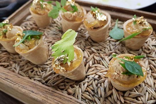 В деревянном ящике с овсом 6 сладковатых кондитерских рожков, наполненных паштетом из фуа-гра, которые украшены лепестками настоящего золота (да, оно съедобно) и зеленью