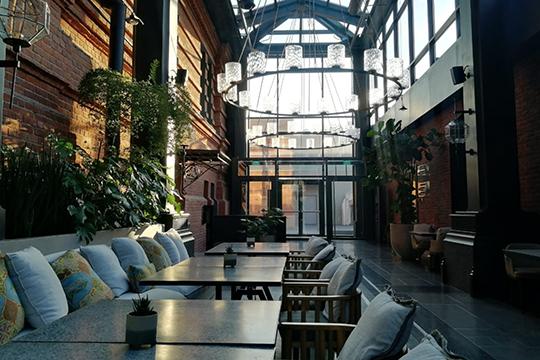 Kazanda Atrium Bar находится вочень светлом пространстве: стены— изкирпичной кладки, повсюду большое количество живых растений, насамом верху— красивая стеклянная крыша