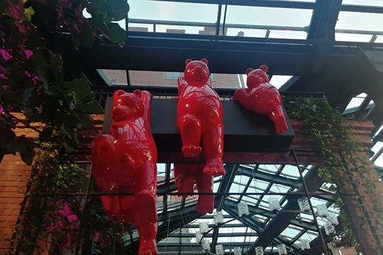 Наодной изстен— инсталляция скрасными лаковыми фигурами медведей, созданная поэскизам турецкого художника-карикатуристаЭрдиля Яшароглу