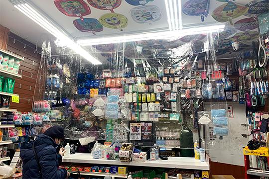 Зона между продавцом и покупателем завешена пленкой. На видном месте расположены маски (справа) и гели-антисептики (слева у кассы)
