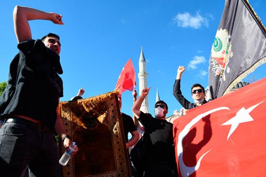 Местные жители с турецкими флагами у собора Святой Софии в Стамбуле, который снова стал мечетью