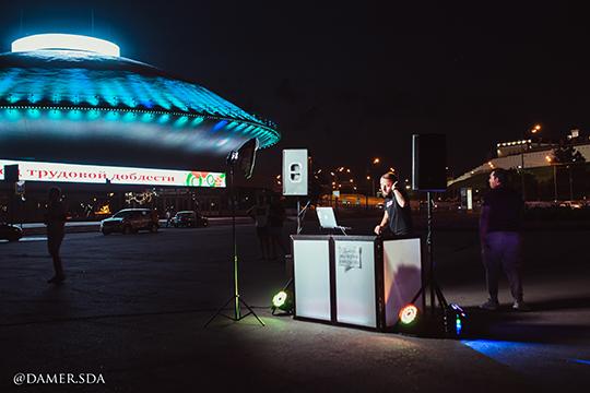 Между цирком и Центральным стадионом на площади Тысячелетия до поздней ночи стоят большие колонки, за которыми молодой человек с бородой и в наушниках