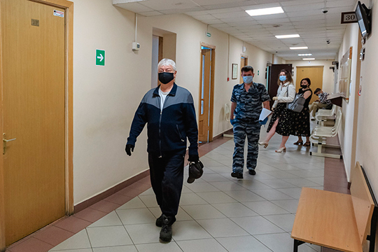 Роберт Мусин приехал в суд с сотрудником ФСИН — в стильной черной маске и черных перчатках. За средствами защиты сложно было разглядеть его лицо