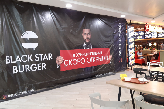 С третьего этажа доносятся ароматы фуд-корта. Поднимаемся. Здесь, пожалуй, картина красуется яркий плакат с рэпером Тимати на обложке и его бургерной Black Star Burger. Даты открытия пока нет