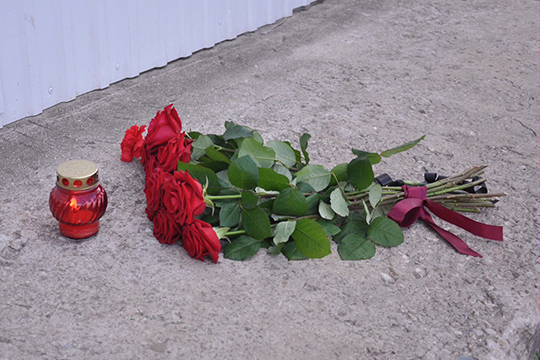 В полутора метрах от входа в офис, где накануне застрелили бизнесмена, рядом с подсохшей лужей крови появились цветы и свечка