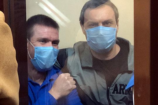 Еникеев (справа) сидел на скамейке внутри аквариума, положив руку на плечи Харламова (слева) и приобняв его. Вдвоем они что-то активно, с улыбкой обсуждали, перешептываясь даже во время чтения приговора