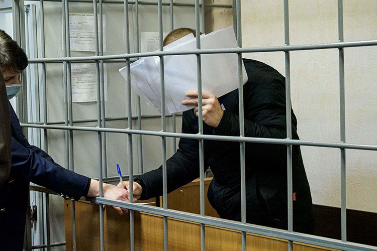 Тагиров повернулся к журналистам спиной, а лицо закрыл листами бумаги. На многочисленные вопросы — об убийствах, о своей семье — он отвечать не стал