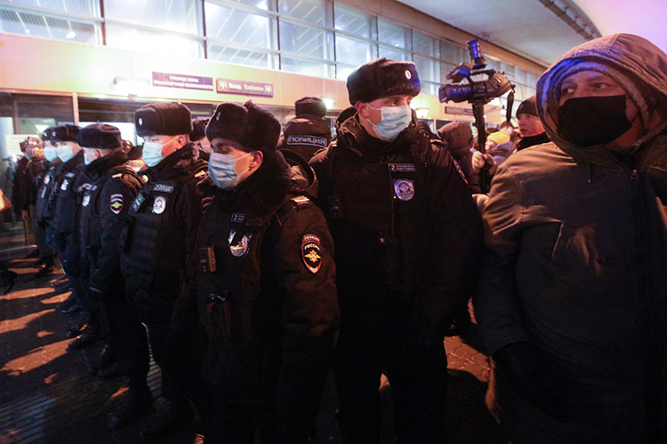 Зачас доназначенного прилета увхода выстроились полицейские иОМОНовцы и, взявшись заруки, надвинулись насторонников Навального ижурналистов и, неразбирая, кто есть кто, всех начали выталкивать намороз