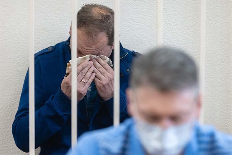 Степущенко, сидя наскамейке зажелезными прутьями, вытирал слезы платком