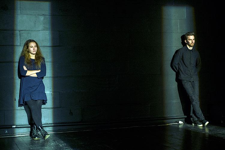 Актеры появляются прямо иззала, спервого ряда. Они становятся усерой стены избетонных блоков, опираются нанее спиной имолчат. Вэто время лучи прожектора помещают ихвузкие световые колбы