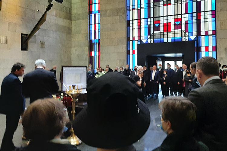 Зал, где проходит церемония— потолки под четыре метра, наодной стене укреплены трубы органа, другая разбита повысоте красно-голубыми витражами— заполнен практически полностью, многие изсобравшихся плачут