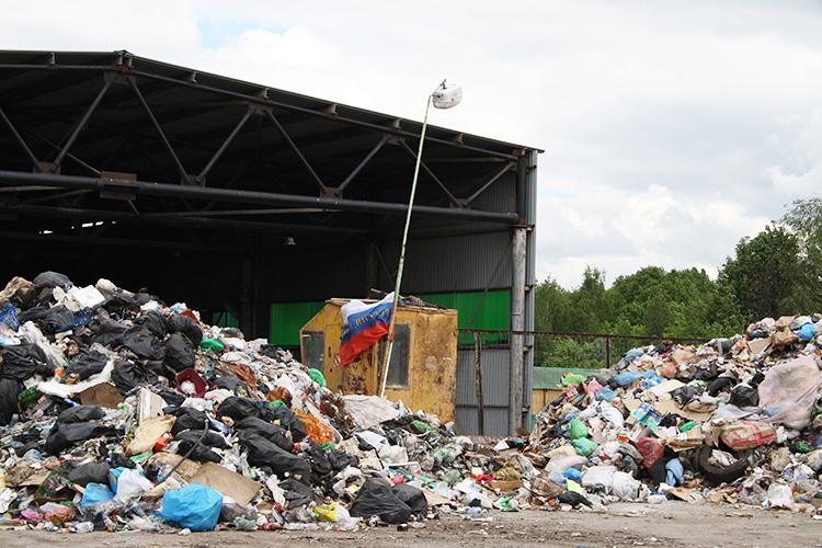 Напротив Самосыровского полигона станция сортировки мусора УК«Экопарк». Наплощадке компании гора отходов, авцентре вагончик сфлагом РФинадписью: «Россия, вперед!»