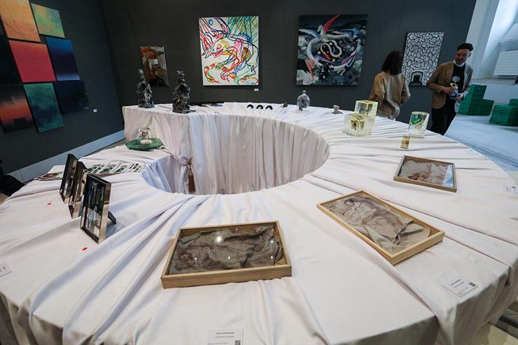 Эстетическое удовольствие итеплые застольные эмоции передает галерея JART, чей стенд вэтом году оформляла группа художниковМишМаш. Вцентре расположился большой закольцованный стол, накрытый праздничной белой скатертью