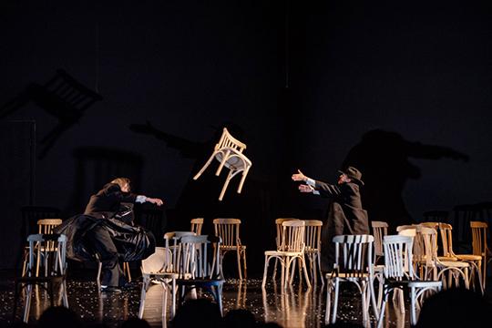 Лаконичная сценография — несомненный плюс спектакля: пара десятков стульев и простыня оказываются в умелых руках режиссера пластичным материалом для раскрытия идеи