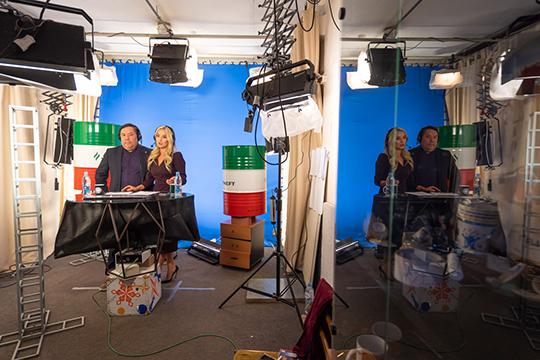 Зухра и Махмуд — на фоне бочек с надписью «Татнефть» и синего экрана, на который наложат видеоряд с арены в Хельсинки