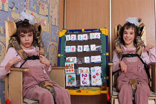 Рите Абдуллаевой и ее сестре-близняшке Веронике 11 лет, у девочек детский церебральный паралич. Им необходимо специализированное кресло-коляска для двойни