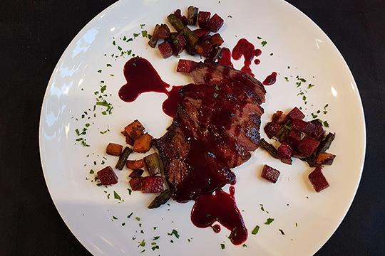 Стейк сирлойн— абстракционизм натарелке изклякс ежевичного соуса, россыпи овощей илегких зеленых брызг покрошенной петрушки вокруг куска мяс