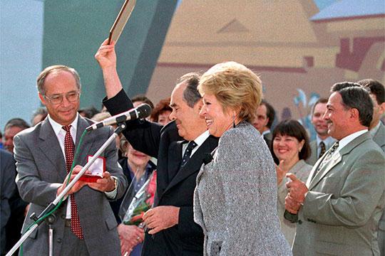 Владимир Егоров (слева) вручает Минтимеру Шаймиеву (в центре) грамоту и медаль за вклад в развитие культуры