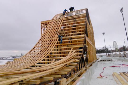 Плотники собирают из деревянных балок остов будущей горки, с ее вершины можно будет прокатиться в две стороны: слева — обычный скат, а справа — маятниковый