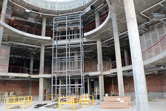 Заходим внутрь, через будущие «револьверные» двери — и попадаем в холл с лифтами и эскалаторами. Всего в здании — 8 пассажирских лифтов и 24 эскалатора