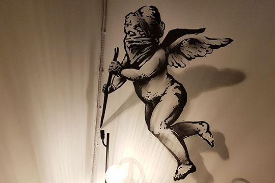 Есть несколько примечательных деталей. В уборной пахнет сыростью, купидон над граффити «Хватит», нарисованный в стиле Бэнкси, замотал лицо платком и отковыривает монтировкой местную электропроводку