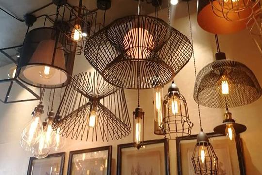 Здесь висят очень любопытные светильники — от лампочек на канатах из проводов под деревянным потолком до стеклянной люстры над коммунальным столом, которая выглядит, как густые мыльные пузыри