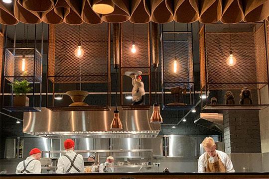 Вцентре внимания— барная стойка почти навесьзал. Она напоминает кухонный гарнитур, закоторым— сама открытая кухня