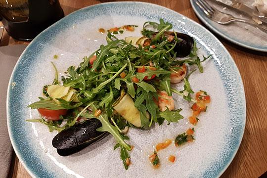 Салат с морепродуктами вполне приличный: с достаточным количеством морских гадов (мидии, кальмары, креветки — стандартное трио), свежей качественной руколой и легкой цитрусовой заправкой