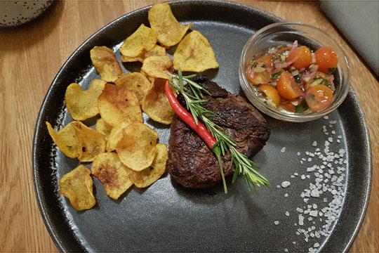 Стейк украшается розмарином и стручком перца, подается с домашними картофельными чипсами (неубедительными) и мисочкой, в которой, по заверениям меню, должны быть «томаты релиш с зеленью и сельдереем»