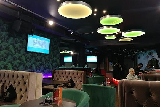 В зале коричневые диваны, зеленые кресла и столы цвета венге. На потолке — круглые плоские люстры тех же цветов. Поддерживает «кокосовую» стилистику стена с изображением пальмовых листьев